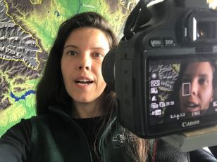Picture of a woman holding a camera to film herself in front of a map.