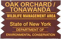 brown sign with yello letters for oak orchard wildlife management area