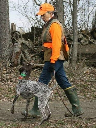 woman in blaze orange vest with her hunting dog