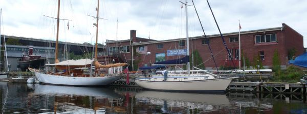 Two sail boats on the water in front of a brick buildings. Laura Heady