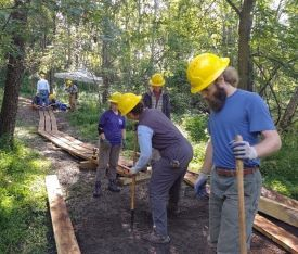 Image depicts five men and women in hard hats with shovels constructing a wooden boardwalk.