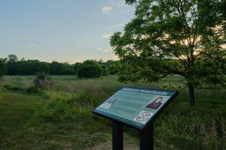 Image depicts view of the sign about the Mohican people in the midst of the floodplain meadow.
