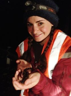 A young woman in a jacket and traffic vest with a head lamp holds a salamander.
