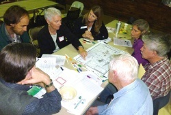 A group of seven people gather around a table covered with maps.