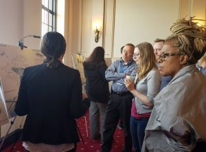 A group of people look at designs displayed on poster boards.