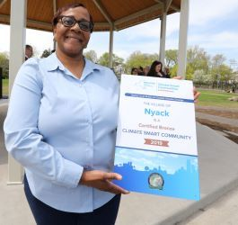 A woman holds a poster that says Nyack is a certified bronze climate smart community