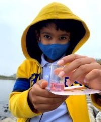 A young boy wearing a mask holds a tube of colored water.