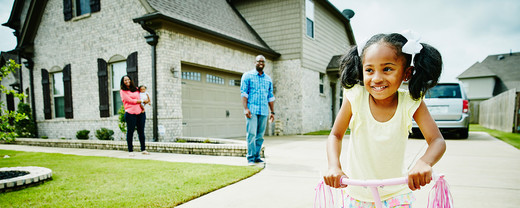 A family with children playing outside their home with car in the driveway.