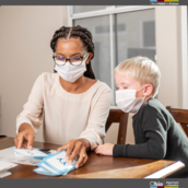 Adult wearing a mask working with an elementary student on flash cards.