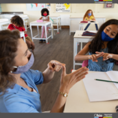 Teacher wearing a face mask working with a student who is also wearing a face mask.
