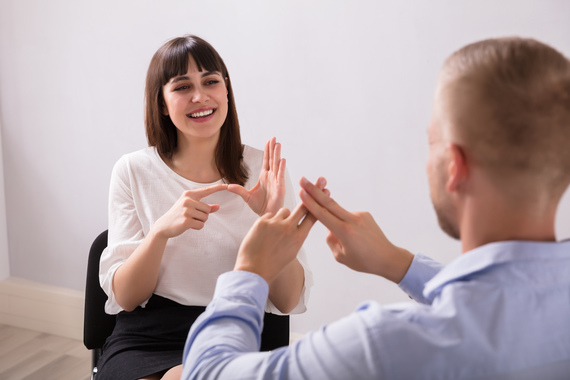 An image of two students communicating through sign language