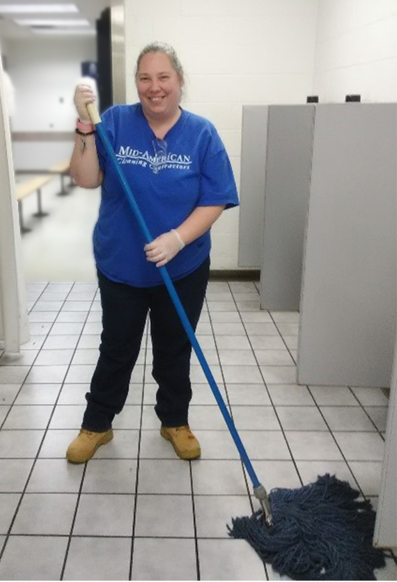 Image of Shannon mopping the floor while smiling