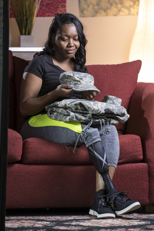 Photo of veteran woman sitting on sofa who is an amputee