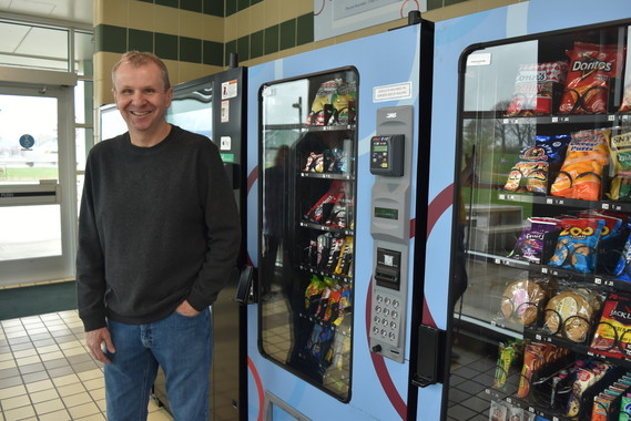 John Canaday standing in front of his vending machines