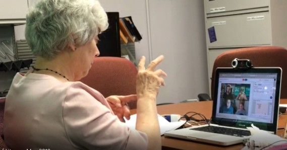 Woman practicing sign language in front of a computer