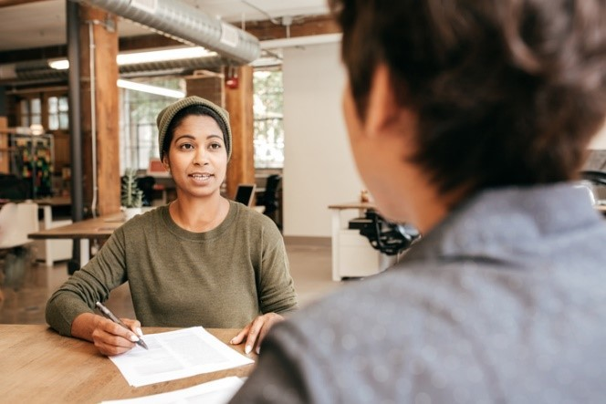 woman at desk taking notes while speaking to another person