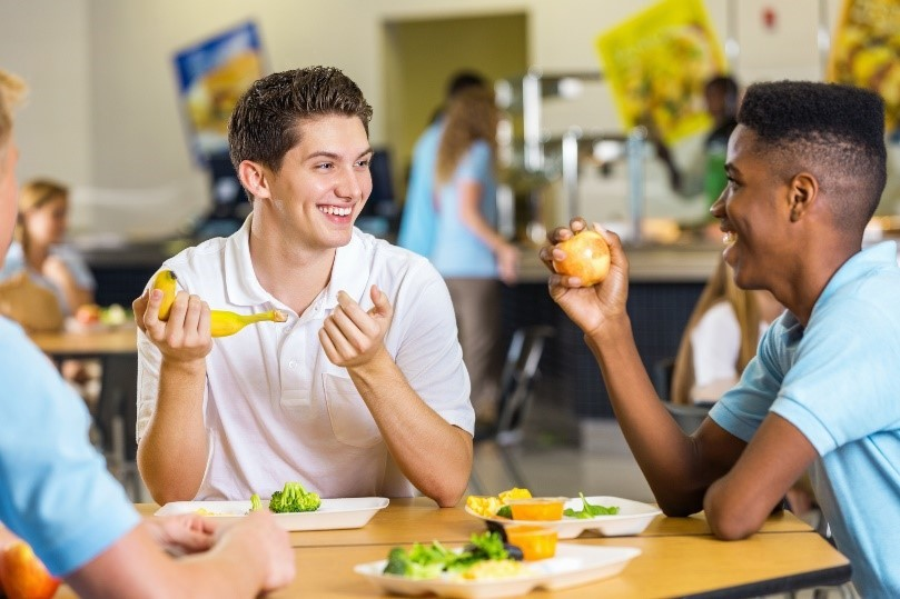 2 male students eating lunch and smiling
