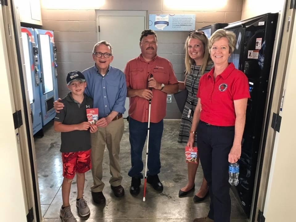 Governor DeWine, his grandson Parker,BE Operator Joe Hall, OOD Staff member Amy Seger, Director of ODNR Mary Mertz standing in Vending area