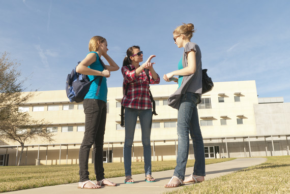 Three girls standing outside of a high school and one is signing