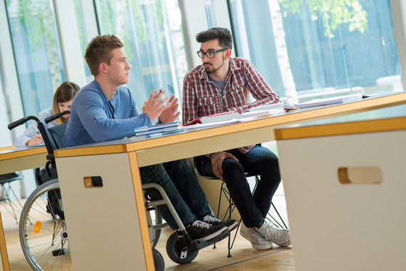 Young man in wheelchair talking with other student in college classroom
