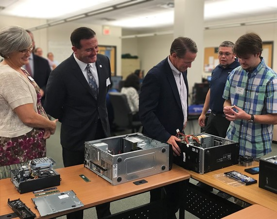 Lt. Governor Jon Husted and OOD Director Kevin Miller looking at computer hardware as student explains Goodwill's IT Program