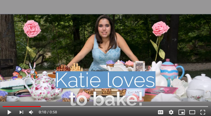 Screen Shot of Facebook Video showing young woman behind table filled with baked goods