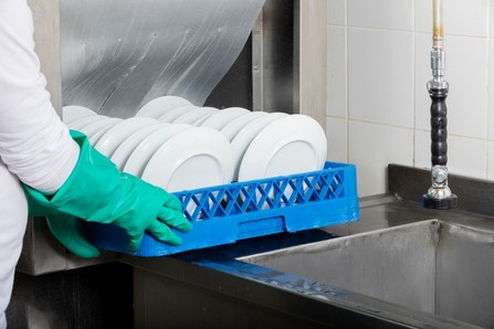 photo of hands guiding tray of dishes into commercial dishwasher