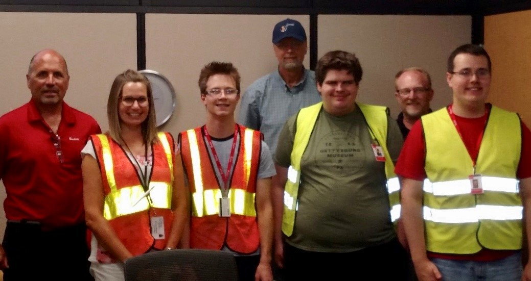 R.W. Beckett staff, job coach, and students with safety vests on.