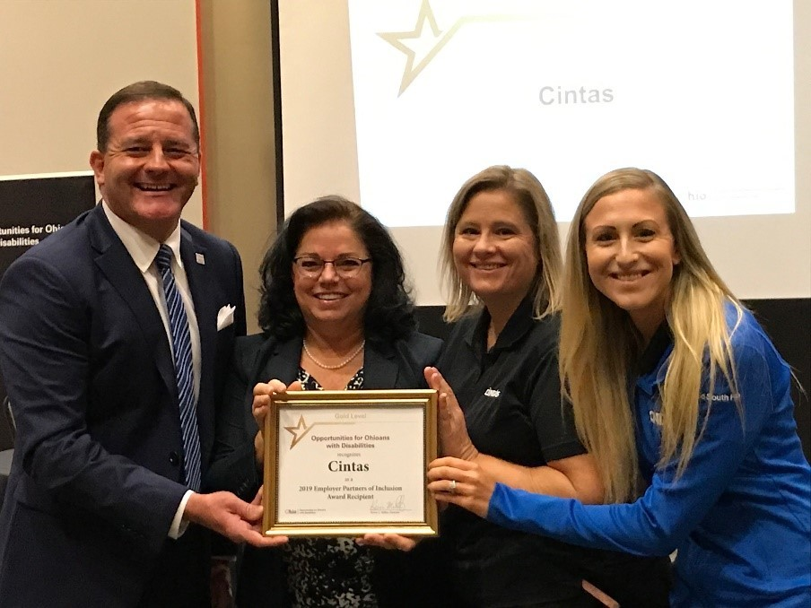 Photo of Director Miller presenting award to Cintas Staff