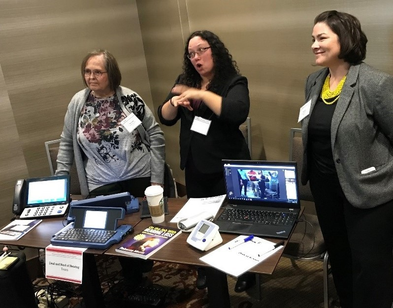 Photo of Verna Mooney, Cathy Vickery and Katie Sheetz demonstrating assistive technology that can benefit the deaf or hard of hearing