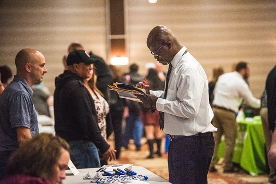 Photo of Carlous Blair taking notes with an employer about an open position at the Canton Job Fair