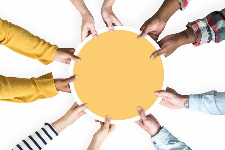 Photo image of hands from different races all grasping a yellow circle