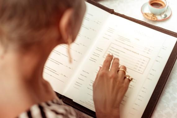Photo looking over a woman's shoulder at a menu