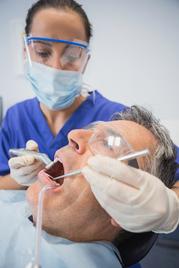 Dentist works on mature man's teeth