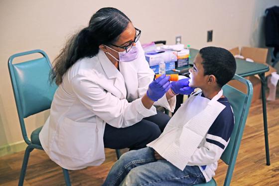 Dr. Courtney Barrett conducts dental screening on young boy