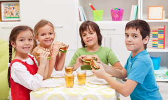 Small group of children eating sandwiches