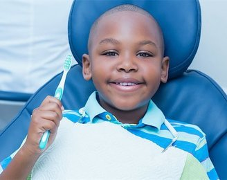 african american young boy holding a toothbrush