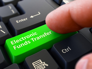 "finger presses green computer key marked ""Electronic Funds Transfer"""