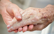 Closeup of young woman's hand holding older woman's frail hand