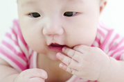 Asian baby with fingers to her mouth