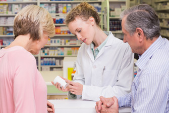 Pharmacist and customer intently discuss prescription at pharmacy counter.