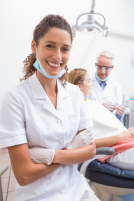 Femaie dental assistant smiling at camera as dentist treats patient in background