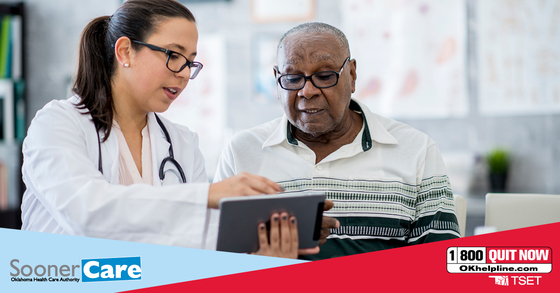 Female doctor points to an electronic tablet while discussing elderly patient's quit plan with him