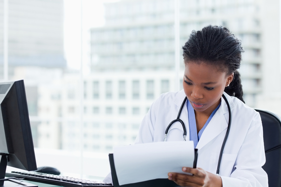 Female doctor adds documentation to medical chart in her office