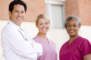 Smiling doctor and nurses standing outside a hospital