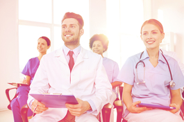 Four smiling health care workers take notes and listen to a presentation in a brightly-lit room