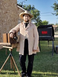 Ambrotype Photographer stands in front of vintage camera