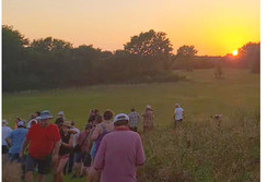 people walking at sunset to view the autumnal equinox