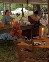 Outdoor tents and lanterns with people in period dres