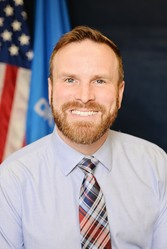 Jason Stephenson headshot in blue shirt and blue and red tie